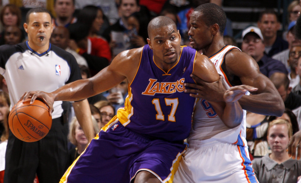 Photo - L.A. LAKERS: Oklahoma City's Serge Ibaka (9) defends Los Angeles' Andrew Bynum (17) during an NBA basketball game between the Oklahoma City Thunder and the Los Angeles Lakers at Chesapeake Energy Arena in Oklahoma City, Thursday, Feb. 23, 2012.  Oklahoma City won 100-85. Photo by Bryan Terry, The Oklahoman