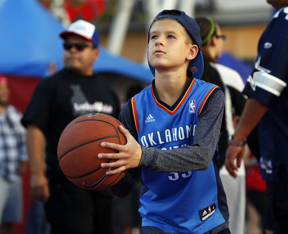 Photo - Thunder fan Chad Carter, 13, of Lake Forest, California, shoots a basket outside the arena before Game 6 of the Western Conference semifinals in the NBA playoffs between the Oklahoma City Thunder and the Los Angeles Clippers at the Staples Center in Los Angeles, Thursday, May 15, 2014. Photo by Nate Billings, The Oklahoman