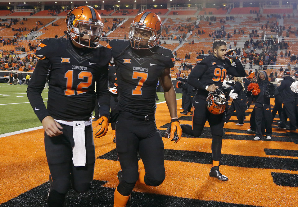 Photo - Oklahoma State's Daxx Garman (12) and Brandon Sheperd (7) walks off the field after the 28-7 loss to Texas during the college football game between the Oklahoma State University Cowboys (OSU) the University of Texas Longhorns (UT) at Boone Pickens Staduim in Stillwater, Okla. on Saturday, Nov. 15, 2014.  Photo by Chris Landsberger, The Oklahoman
