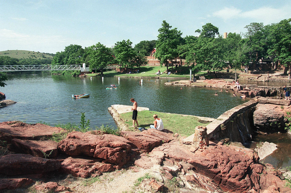Photo - Medicine Park Creek becomes a favorite swimming hole during the hot summer months in Medicine Park, Ok.  The newly built bridge can be seen in the background. OKLAHOMAN ARCHIVE PHOTO