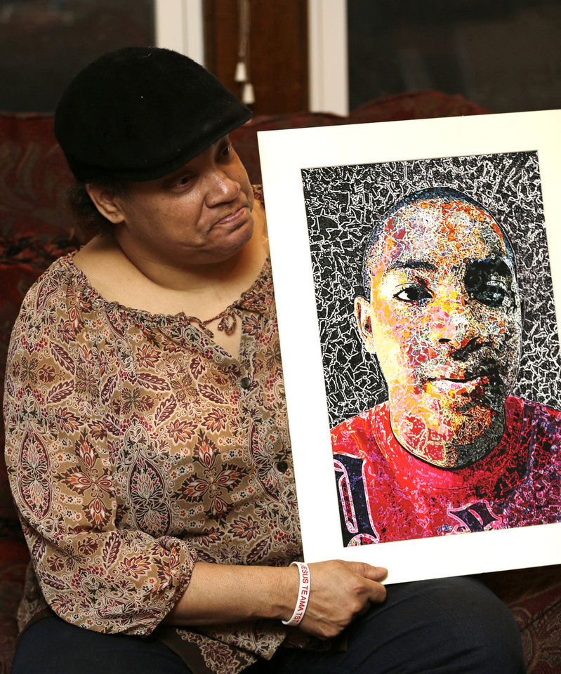 Photo - Lisa Williamson holds up a self-portrait of her son Brandon Murray, Monday, March 11, 2013, in Warren, Ohio. Investigators spent Monday trying to piece together why eight teenagers were crammed into a speeding SUV without the owner's permission when it flipped over into a pond, killing six of them, including Murray. (AP Photo/Tony Dejak)