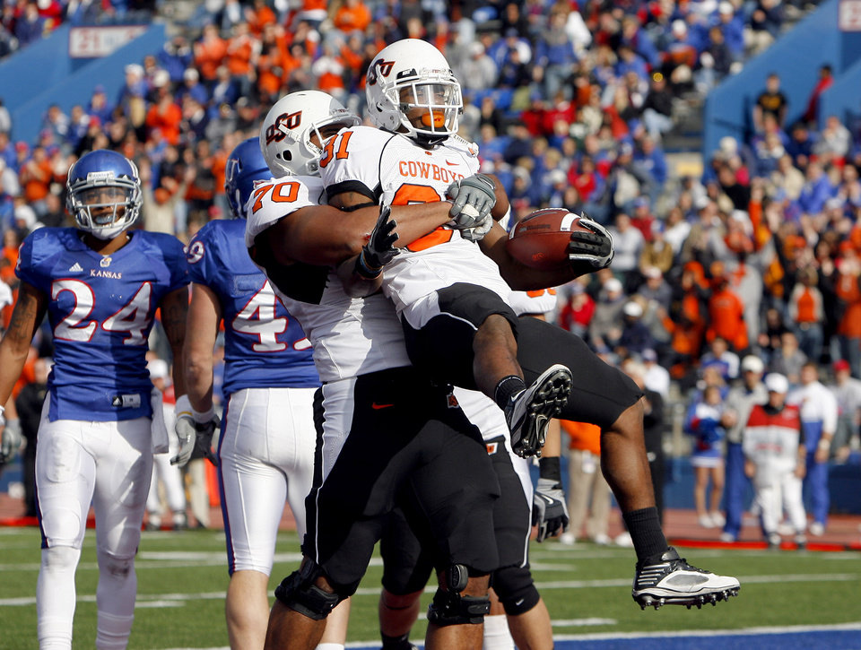 Photo - Oklahoma State's Jeremy Smith (31) and Oklahoma State's Jonathan Rush (70) celebrate a touchdown during the college football game between Oklahoma State (OSU) and Kansas (KU), Saturday, Nov. 20, 2010 at Memorial Stadium in Lawrence, Kan. Photo by Sarah Phipps, The Oklahoman