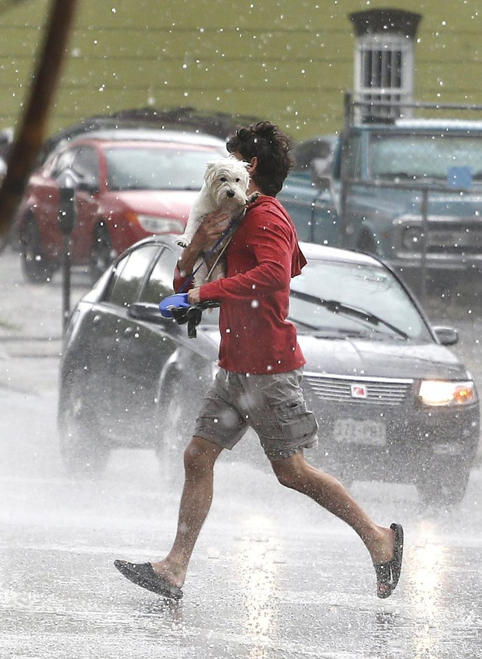 Photo - A man runs across the street carrying his dog, as a hail storm falls over downtown Denver, Thursday May 22, 2014. More spring thunderstorms began rolling into the Front Range and eastern Colorado on Thursday, a day after six tornadoes touched down east of Denver. Heavy hail was reported in Red Feather Lakes northwest of Fort Collins, and more hail is falling in Denver. (AP Photo/Brennan Linsley)