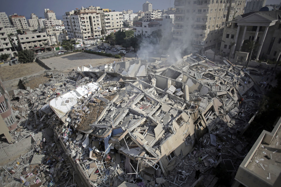 Photo - Smoke rises from the rubble of the Al-Zafer apartment tower following Israeli airstrikes Saturday that collapsed the 12-story building, in Gaza City, Sunday, Aug. 24, 2014. The targeting of large buildings appears to be part of a new military tactic by Israel. (AP Photo/Khalil Hamra)