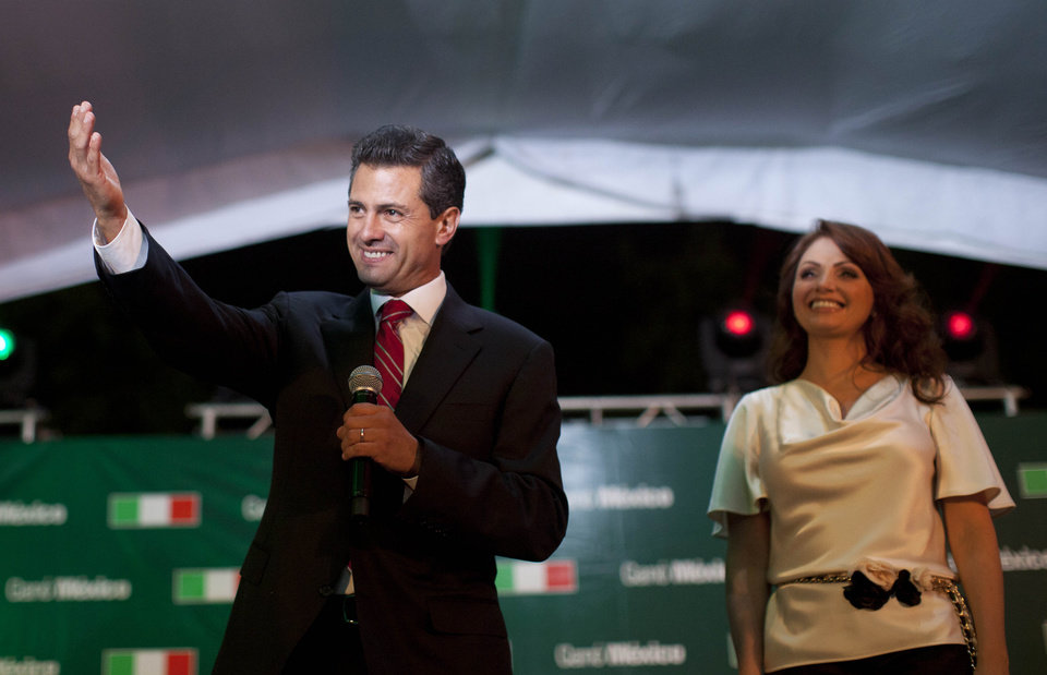 Photo -   Enrique Pena Nieto, presidential candidate for the Revolutionary Institutional Party (PRI), left, speaks to supporters accompanied by his wife Angelica Rivera at the party's headquarters in Mexico City, early Monday, July 2, 2012. Mexico's old guard sailed back into power after a 12-year hiatus Sunday as the official preliminary vote count handed a victory to Pena Nieto, whose party was long accused of ruling the country through corruption and patronage. (AP Photo/Alexandre Meneghini)