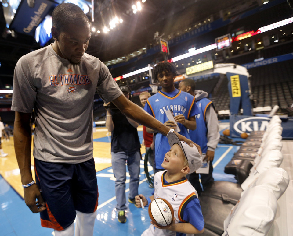 Photo - Oklahoma City 's Kevin Durant (35) greets Hunter Halvorson as part of his Make-A-Wish before  the NBA game between the Oklahoma City Thunder and the Utah Jazz at the Chesapeake Energy Arena, Sunday, March 30, 2014, in Oklahoma City. Photo by Sarah Phipps, The Oklahoman