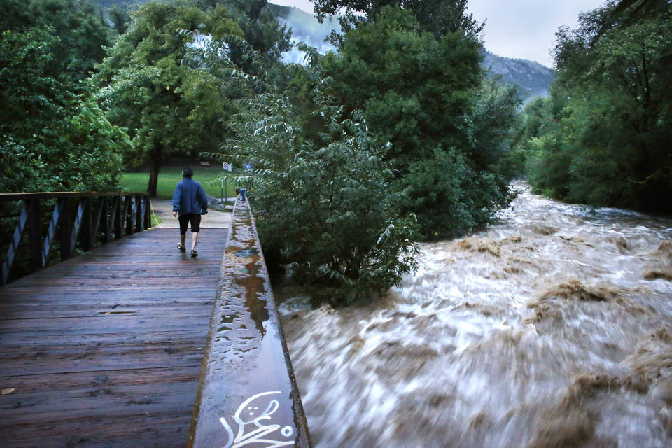 Photo - During a break in the rain, a woman walks over a footbridge past Boulder Creek which roils at high speed after days of record rain and flooding, at the base of Boulder Canyon,  Friday Sept. 13, 2013 in Boulder, Colo.  People in Boulder were ordered to evacuate as water rose to dangerous levels amid a storm system that has been dropping rain for a week. Rescuers struggled to reach dozens of people cut off by flooding in mountain communities, while residents in the Denver area and other areas were warned to stay off flooded streets. (AP Photo/Brennan Linsley)