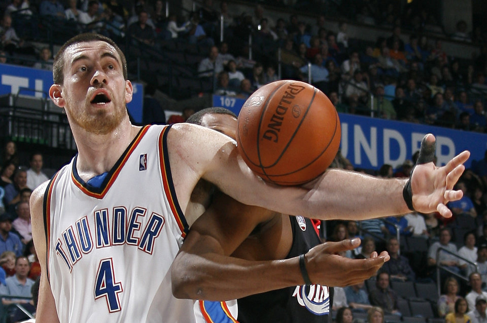 Photo - Oklahoma City's Nick Collison (4) grabs a rebound during the NBA basketball game between the Oklahoma City Thunder and Philadelphia at the Ford Center, Sunday, March 8, 2009, in Oklahoma City . PHOTO BY SARAH PHIPPS, THE OKLAHOMAN ORG XMIT: KOD