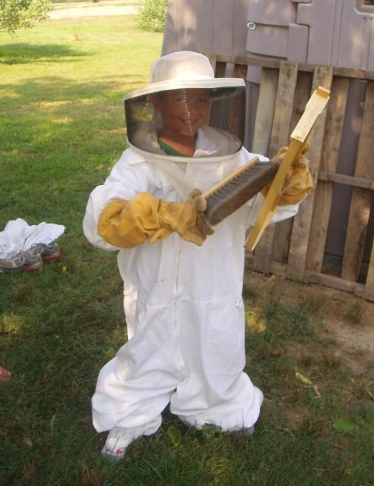 Photo - Jacques Adams does a little beekeeping at Wild Things Farm. (Photo by Happy Frazier)