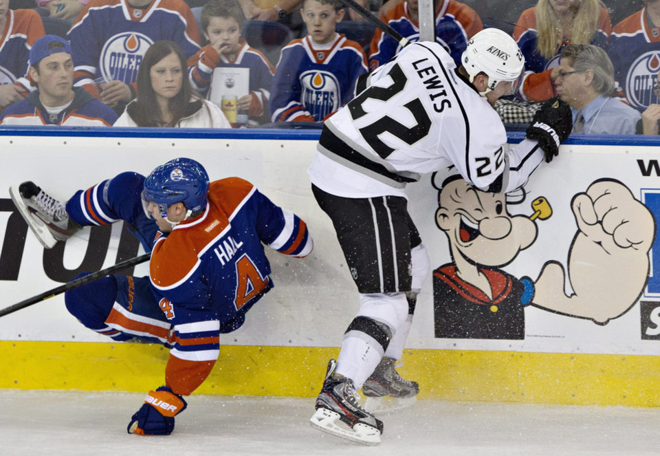 Los Angeles Kings' Trevor Lewis, right, checks Edmonton Oilers' Taylor Hall during second period NHL hockey action in Edmonton, Alberta, on Tuesday Feb. 19, 2013. (AP Photo/THE CANADIAN PRESS,Jason Franson)