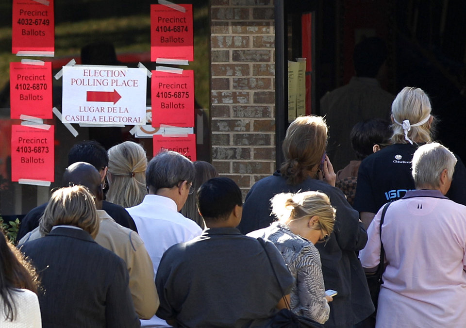Information signs guide voters inside a polling location as they line up to cast their votes Tuesday, Nov. 6, 2012, in Dallas. After a grinding presidential campaign, Americans head into polling places across the country. (AP Photo/Tony Gutierrez)