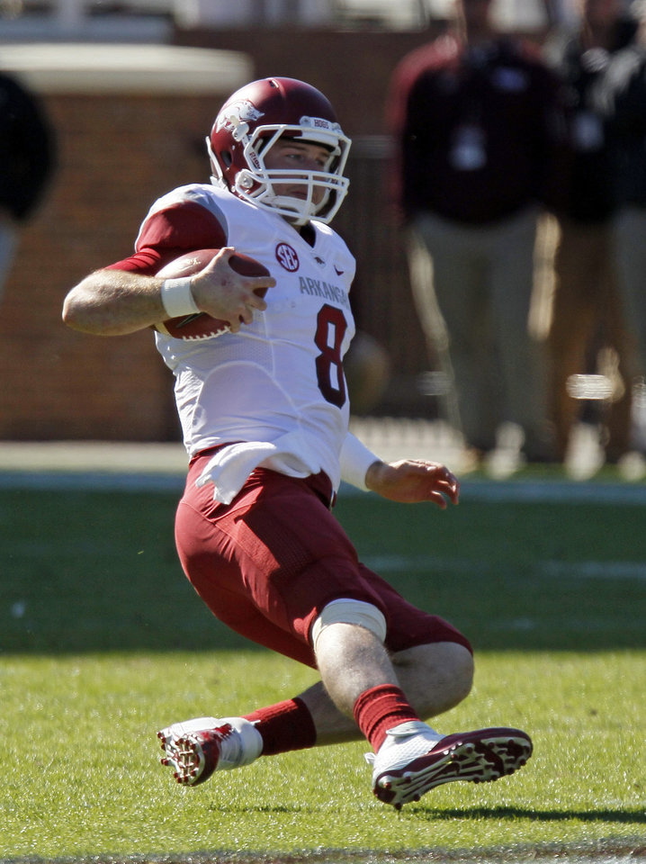 Photo -   Arkansas quarterback Tyler Wilson (8) begins to slide for a first down in the first quarter of their NCAA college football game against Mississippi State in Starkville, Miss., Saturday, Nov. 17, 2012. (AP Photo/Rogelio V. Solis)