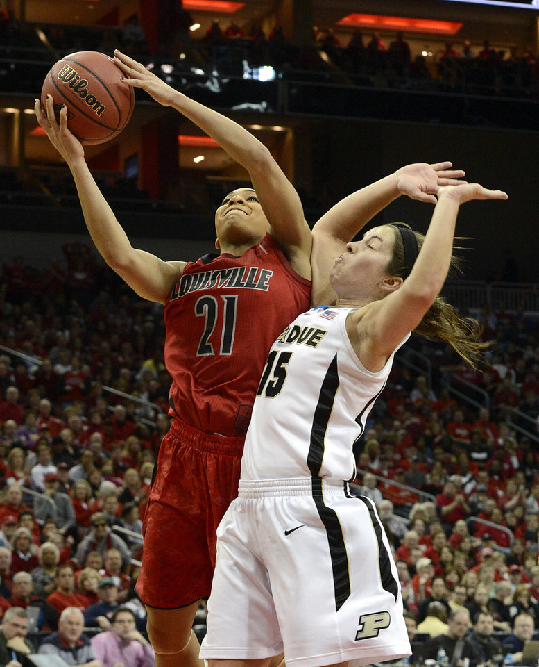 Louisville's Bria Smith, left, puts a shot up past the defense of Purdue's Courtney Moses during the first half of their second round game in the women's NCAA college basketball tournament in Louisville, Ky., Tuesday March 26, 2013. (AP Photo/Timothy D. Easley)