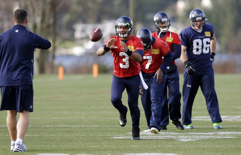 Photo - Seattle Seahawks quarterback Russell Wilson (3) has a ball tossed to him during stretching drills before NFL football practice, Friday, Jan. 3, 2014, in Renton, Wash. Seattle plays at home in a playoff game on Jan. 11. (AP Photo/Ted S. Warren)