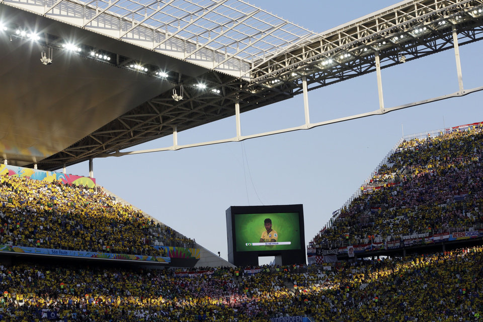 Photo - Brazil's Neymar's image is displayed on a video screen as players are introduced before the group A World Cup soccer match between Brazil and Croatia, the opening game of the tournament, in the Itaquerao Stadium in Sao Paulo, Brazil, Thursday, June 12, 2014.  (AP Photo/Andre Penner)