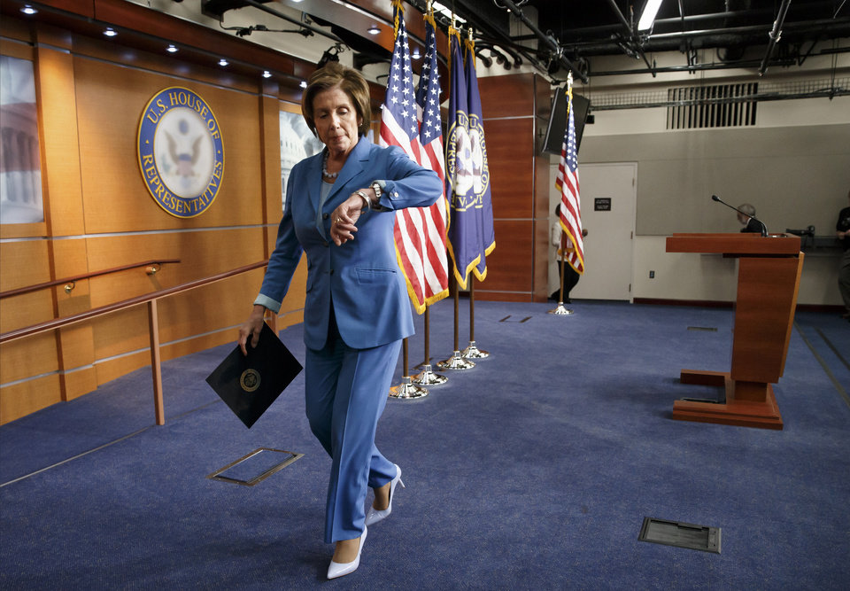 On the last day before Congress takes a five-week summer recess, House Minority Leader Nancy Pelosi, D-Calif., checks her watch for a scheduled vote after speaking to reporters on Capitol Hill in Washington, Thursday, July 31, 2014. Yesterday, Republicans pushed through legislation to launch a campaign-season lawsuit against President Barack Obama, accusing him of deliberately exceeding the bounds of his constitutional authority, Democrats have branded the effort a political charade and an effort by top Republicans to mollify conservatives who want Obama to be impeached. (AP Photo/J. Scott Applewhite)