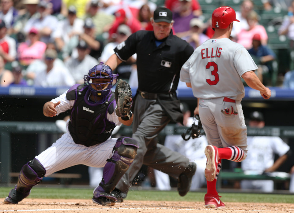 Photo - St. Louis Cardinals' Mark Ellis, right, scores on a sacrifice fly hit by Matt Carpenter as Colorado Rockies catcher Wilin Rosario, left, fields the throw under the watch of home plate umpire Ted Barrett in the fifth inning of a baseball game in Denver on Wednesday, June 25, 2014. (AP Photo/David Zalubowski)
