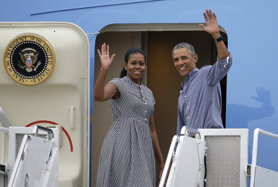 Photo - President Barack Obama, right, and first lady Michelle Obama wave as they board Air Force One at the Cape Cod Coast Guard Station in Bourne, Mass., Sunday, Aug. 21, 2016. President Obama and the first family are returning to Washington D.C. following their vacation on the island of Martha's Vineyard in Massachusetts. (AP Photo/Steven Senne)