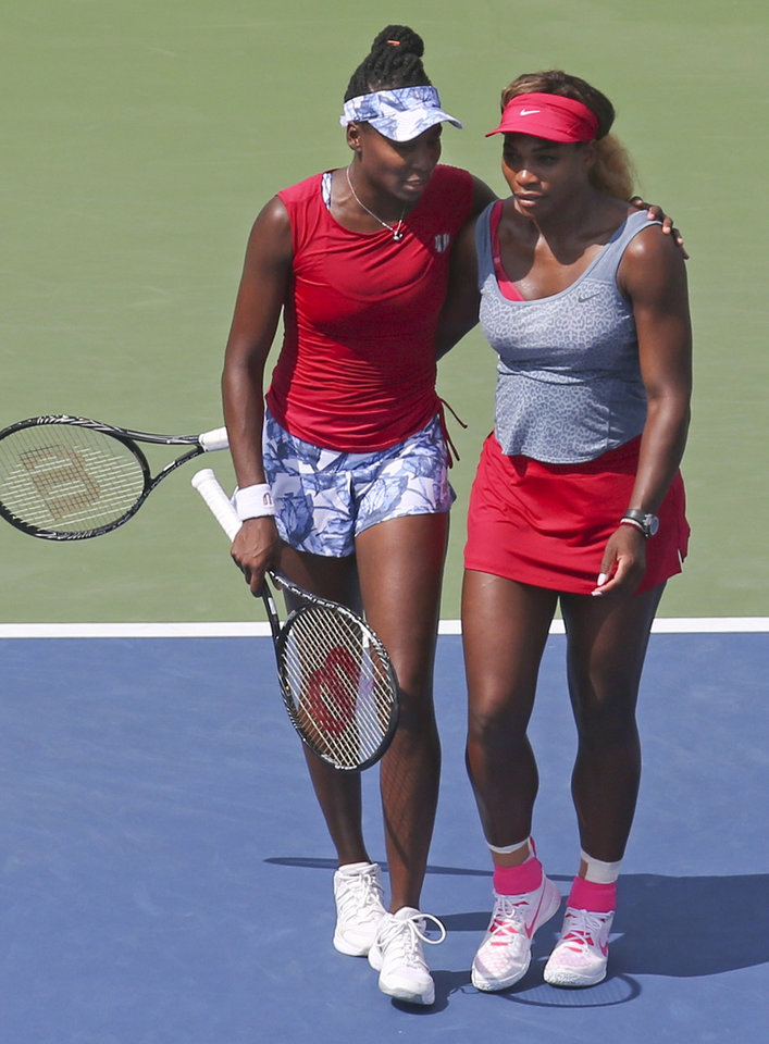Photo - Venus, left, and Serena Williams walk to mid court after losing a quarterfinals doubles match to Ekaterina Makarova and Elena Vesnina, of Russia, during the 2014 U.S. Open tennis tournament, Tuesday, Sept. 2, 2014, in New York. (AP Photo/John Minchillo)
