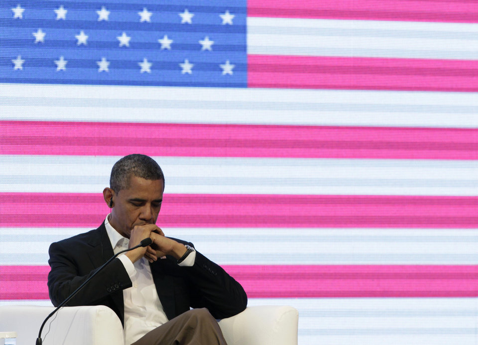 Photo -   President Barack Obama sits in front of a large video screen displaying an image of a U.S. national flag during a three-way conversation with Brazil's President Dilma Rousseff and Colombia's President Juan Manuel Santos, not pictured, at the CEO Summit of the Americas in Cartagena, Colombia, Saturday April 14, 2012. Regional business leaders are meeting parallel to the sixth Summit of the Americas which brings together presidents and prime ministers from Canada, the Caribbean, Latin America and the U.S. (AP Photo/Carolyn Kaster)