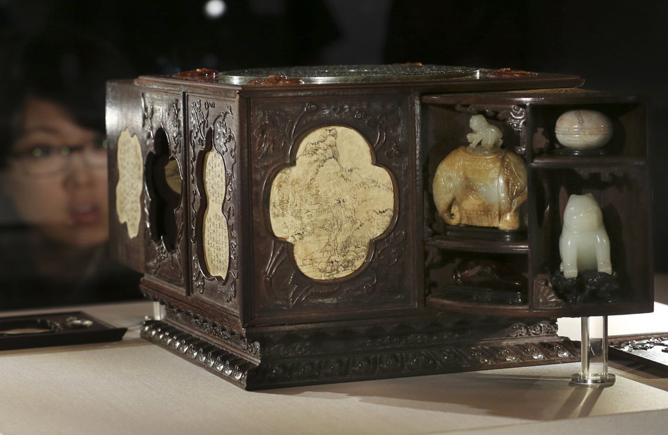 Photo - A woman looks at the square sandalwood curio box with multiple treasures of Qing dynasty displayed in Tokyo during a press preview of the exhibition of