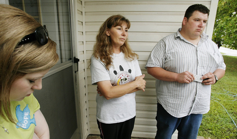 Photo - Pam Williams Gray, center, and Michael Williams, right, stand with an unidentified woman on the front porch of their brother's house in Seminole, Okla., Monday afternoon as a steady stream of visitors came to pay their respects to their family after their brother, Marvin Williams, and a fellow Seminole County deputy were gunned down Sunday afternoon. Ezekiel Holbert, 26, is charged in their deaths.  Photo by Jim Beckel, The Oklahoman