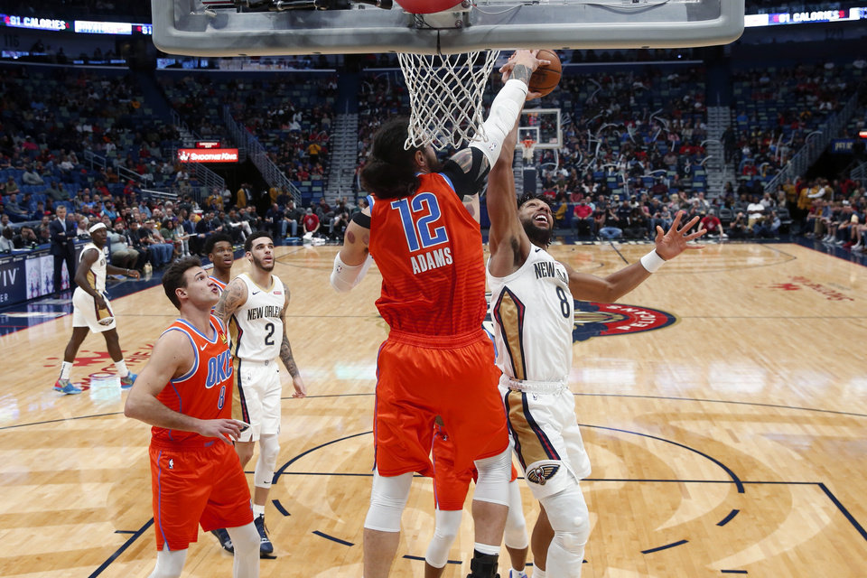 Photo - Oklahoma City Thunder center Steven Adams (12) blocks a shot by New Orleans Pelicans center Jahlil Okafor (8) in the first half of an NBA basketball game in New Orleans, Sunday, Dec. 1, 2019. (AP Photo/Gerald Herbert)