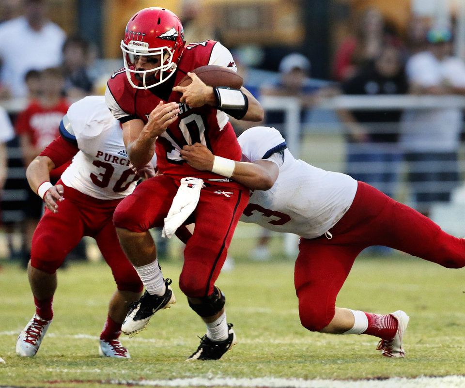 Photo - Washington quarterback Brock Harmon is brought down by Purcell's Jake Combest (30) and Austin Pendley in high school football on Friday, Sept. 13, 2013 in Washington, Okla.  Photo by Steve Sisney, The Oklahoman