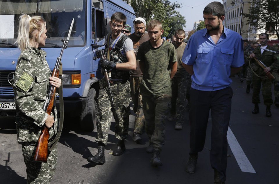 Photo - Pro-Russian rebels escort captured Ukrainian army prisoners in a central square in Donetsk, eastern Ukraine, Sunday, Aug. 24, 2014. Ukraine has retaken control of much of its eastern territory bordering Russia in the last few weeks, but fierce fighting for the rebel-held cities of Donetsk and Luhansk persists. (AP Photo/Sergei Grits)