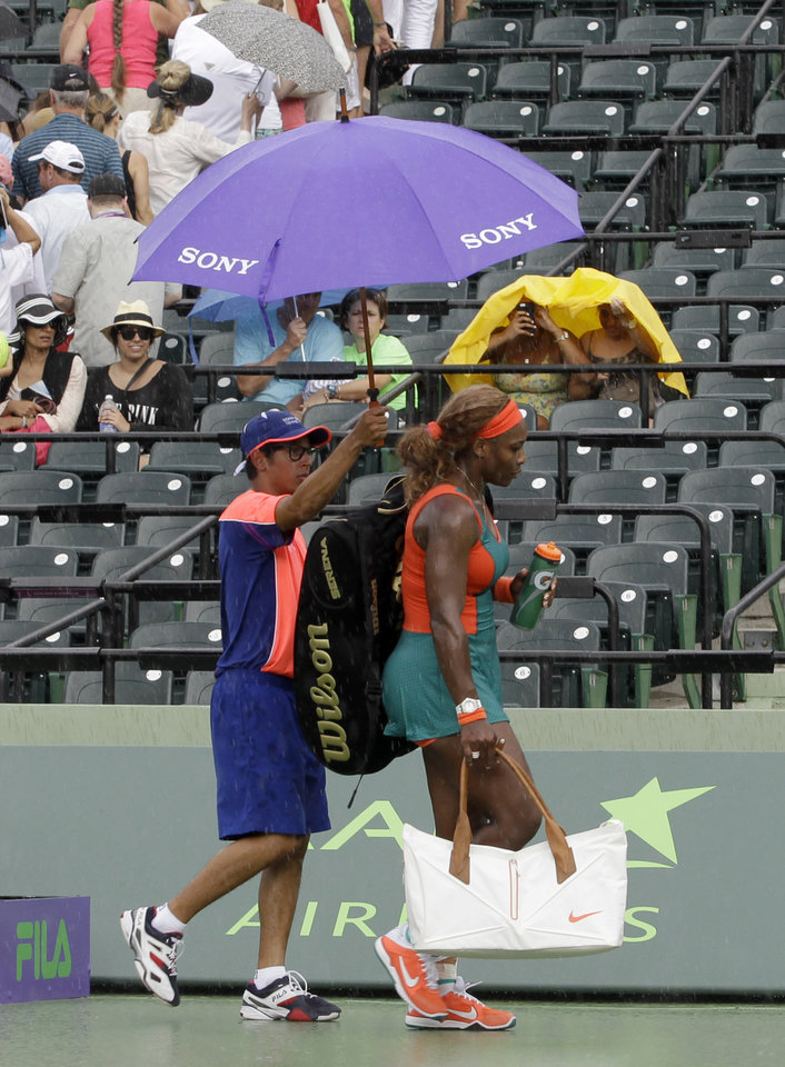 Photo - Serena Williams, of the United States, walks off the court as it begins to rain during her match against Caroline Garcia, of France, at the Sony Open tennis tournament in Key Biscayne, Fla., Saturday, March 22, 2014. (AP Photo/Alan Diaz)