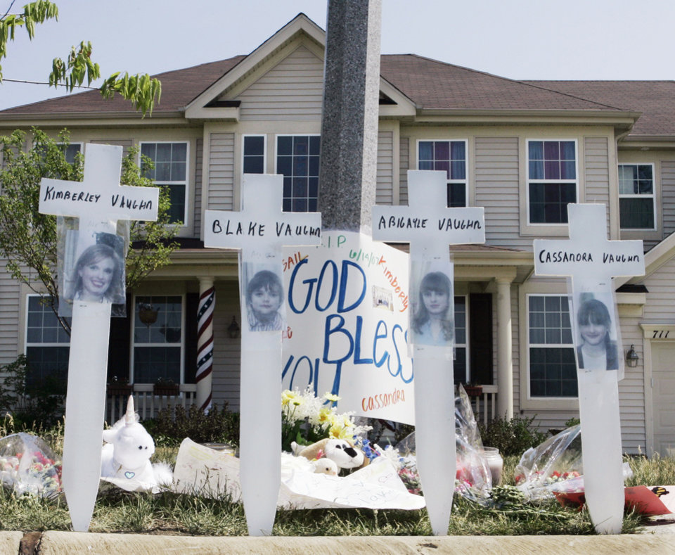 Photo -   FILE - In this June 15, 2007 file photo, a makeshift memorial to Kimberly Vaughn, and her three children Abigayle, 12, Cassandra, 11, and Blake, 8, is seen outside their home in Oswego, Ill. Closing statements are scheduled to begin Thursday, Sept. 20, 2012, in Joliet, Ill., in the murder trial for Christopher Vaughn, accused of shooting dead his wife Kimberly and three kids as the family drove to a waterpark in 2007. (AP Photo/Charles Rex Arbogast, File)