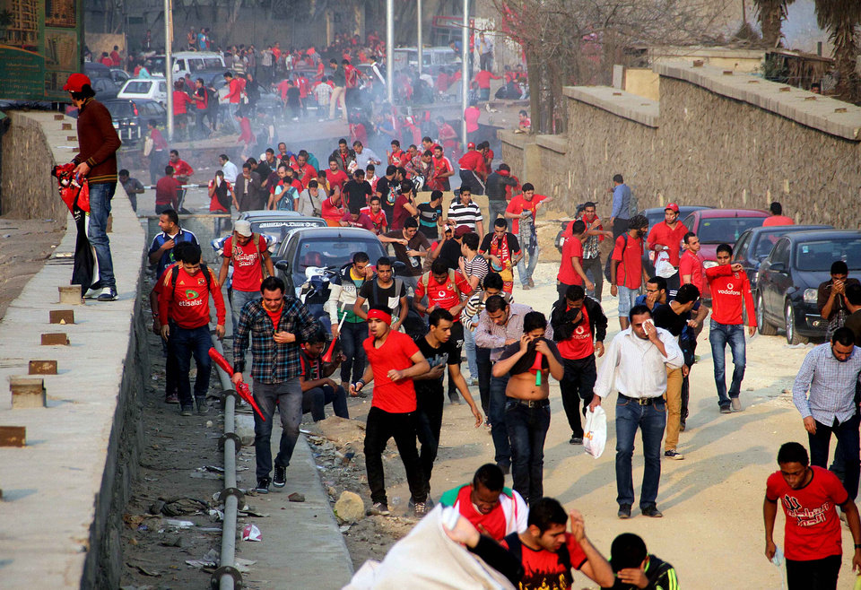 Photo - Supporters of Egyptian club Al Ahly run from tear gas during clashes with police outside a stadium ahead of the African Champions League final in Cairo, Egypt, Sunday, Nov. 10, 2013. Police used tear gas Sunday to disperse the crowd as they threw rocks and tried to push their way into the stadium, many with no tickets. (AP Photo/Mostafa Darwish)