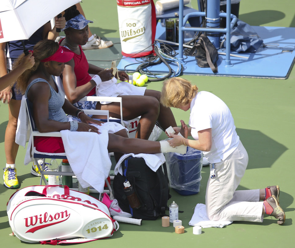 Photo - Serena Williams, left, has her angle re-taped as Venus Williams looks on during a break between games during a quarterfinals doubles match against Elena Vesnina and Ekaterina Makarova at the 2014 U.S. Open tennis tournament, Tuesday, Sept. 2, 2014, in New York. (AP Photo/John Minchillo)