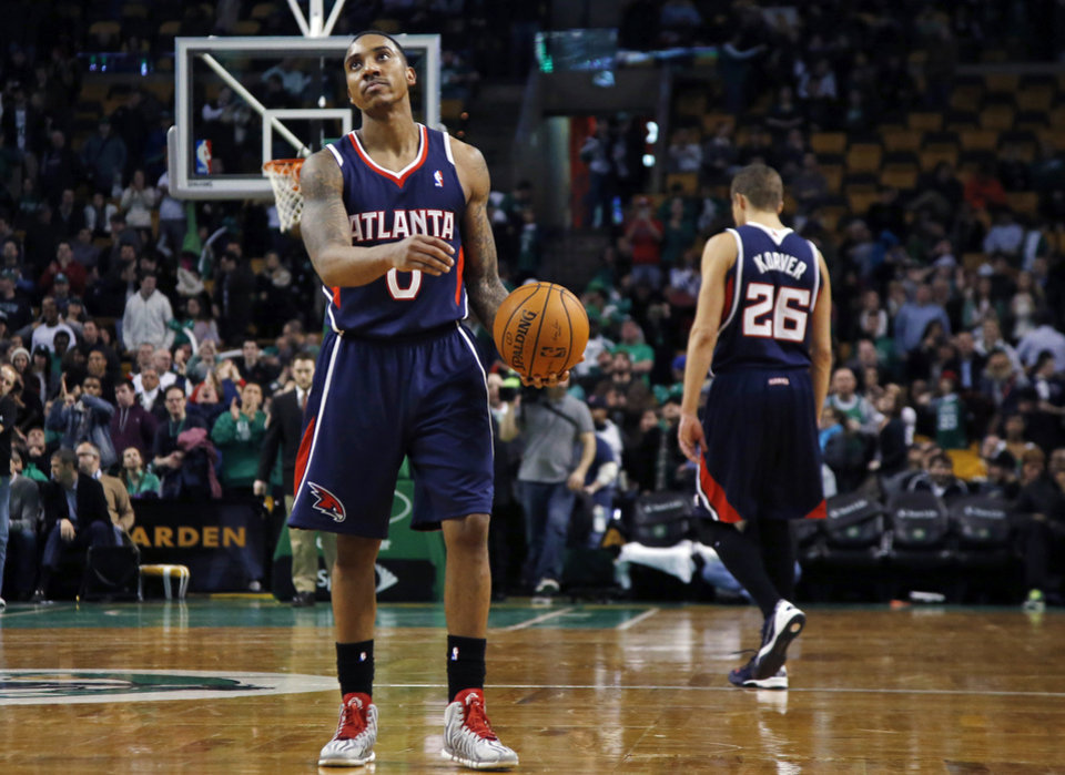 Photo - Atlanta Hawks guard Jeff Teague (0) holds the ball while teammate Kyle Korver (26) walks off the court as time runs out in the Hawks' 115-104 loss to the Boston Celtics in an NBA basketball game in Boston, Wednesday, Feb. 26, 2014. (AP Photo/Elise Amendola)