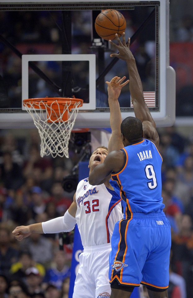 Photo - Oklahoma City Thunder forward Serge Ibaka, right, of Congo, puts up a shot as Los Angeles Clippers forward Blake Griffin defends during the first half of their NBA basketball game, Tuesday, Jan. 22, 2013, in Los Angeles.  (AP Photo/Mark J. Terrill)  ORG XMIT: LAS103