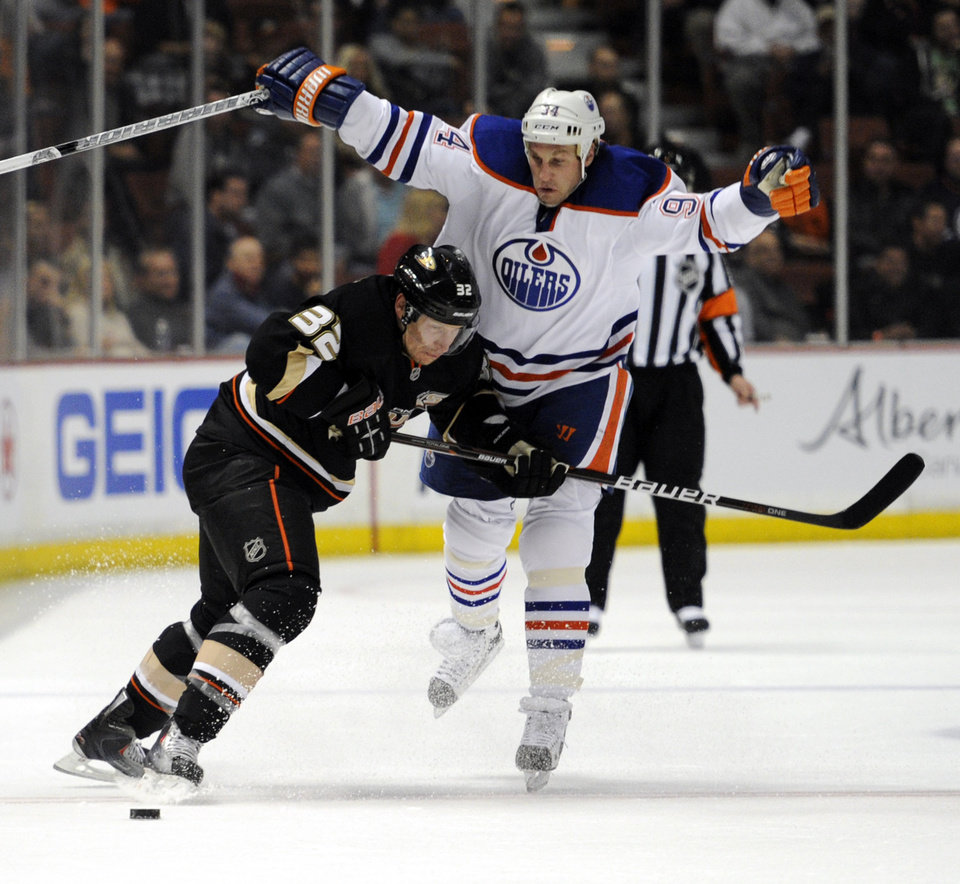 Photo -   Anaheim Ducks defenseman Toni Lydman (32), of Finland, and Edmonton Oilers left wing Ryan Smyth (94) battle for the puck in the period of an NHL hockey game in Anaheim, Calif., Monday, March 5, 2012. (AP Photo/Lori Shepler)