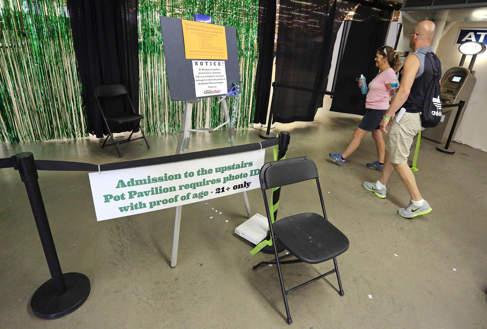 Photo - Visitors enter the pot pavilion at Denver County Fair, the nation's first county fair to allow pot competitions, in Denver, Friday Aug. 1, 2014. There's no actual weed at the fairgrounds. Instead, fairgoers will see photos of competing pot plants and marijuana-infused foods. A sign near the entry warns patrons not to consume pot at the fair. (AP Photo/Brennan Linsley)