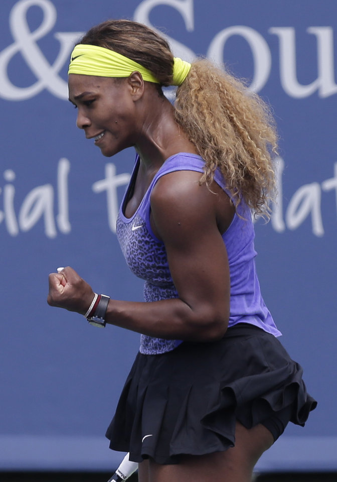 Photo - Serena Williams clinches her fist after hitting a shot against Samantha Stosur, from Australia, during a match at the Western & Southern Open tennis tournament, Wednesday, Aug. 13, 2014, in Mason, Ohio. (AP Photo/Al Behrman)