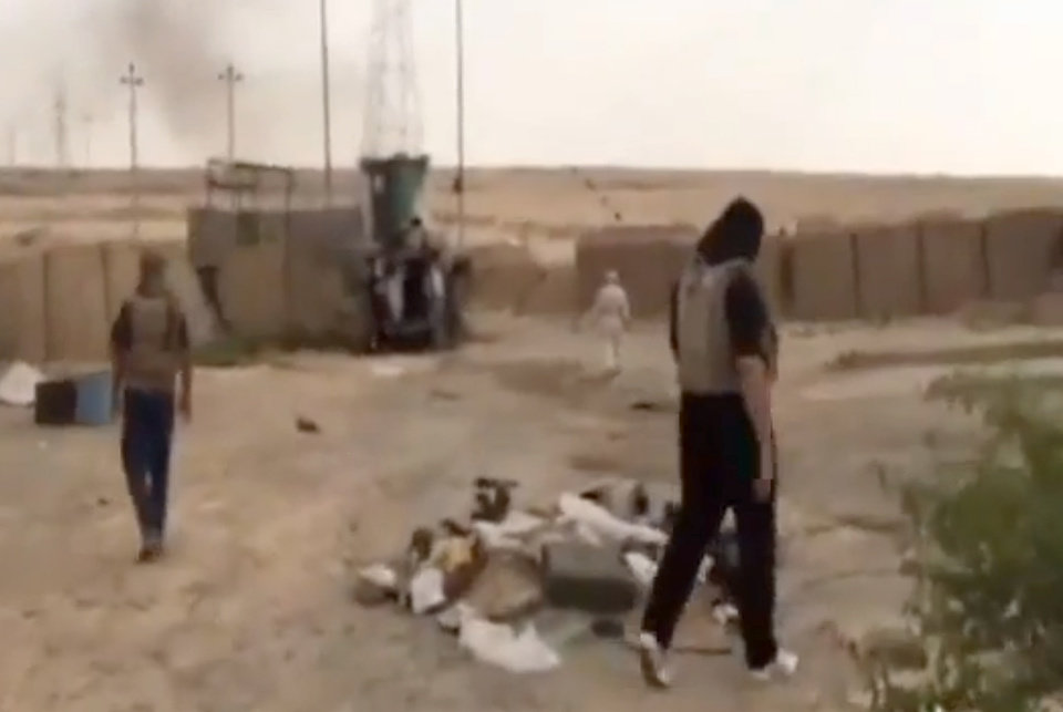 Photo - This image made from video posted by Iraqi0Revolution, a group supporting the al-Qaida breakaway Islamic State of Iraq and the Levant (ISIL) on Wednesday, June 12, 2014, which has been verified and is consistent with other AP reporting, shows militants on Al-Sharqat base north of Tikrit, Iraq. The al-Qaida-inspired group that led the charge in capturing two key Sunni-dominated cities in Iraq this week has vowed to march on to Baghdad, raising fears about the Shiite-led government's ability to slow the assault following lightening gains. Fighters from ISIL on Wednesday took Saddam Hussein's hometown of Tikrit, as soldiers and security forces abandoned their posts and yielded ground once controlled by U.S. forces. (AP Photo/Iraqi0Revolution via AP video)
