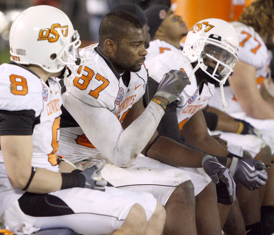 Photo - OSU's Brandon Pettigrew, center, and Dez Bryant, right, sit on the bench during the final seconds of their loss in the Holiday Bowl college football between Oklahoma State and Oregon at Qualcomm Stadium in San Diego, Tuesday, Dec. 30, 2008.  PHOTO BY BRYAN TERRY, THE OKLAHOMAN.