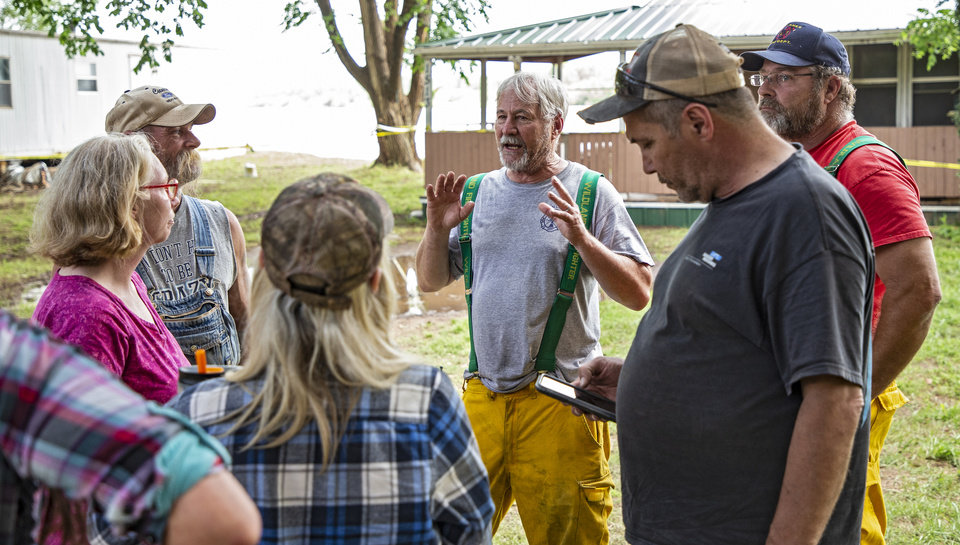 Photo - Fire Chief Mike Gilliam, center, talks with Twin Lakes residents as flood waters from the Cimarron River threaten homes in the Twin Lakes community near Cimarron City, Okla. on Wednesday, May 22, 2019.  [Chris Landsberger/The Oklahoman]