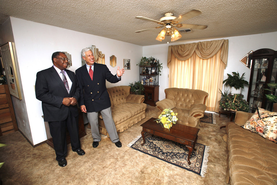 Homeowner Tommy Johnson with auctioneer Louis Dakil in Johnson's living room at 424 NW 91. The home is one of more than 40 properties Dakil will auction on Thursday evening. <strong>PAUL B. SOUTHERLAND - The Oklahoman</strong>