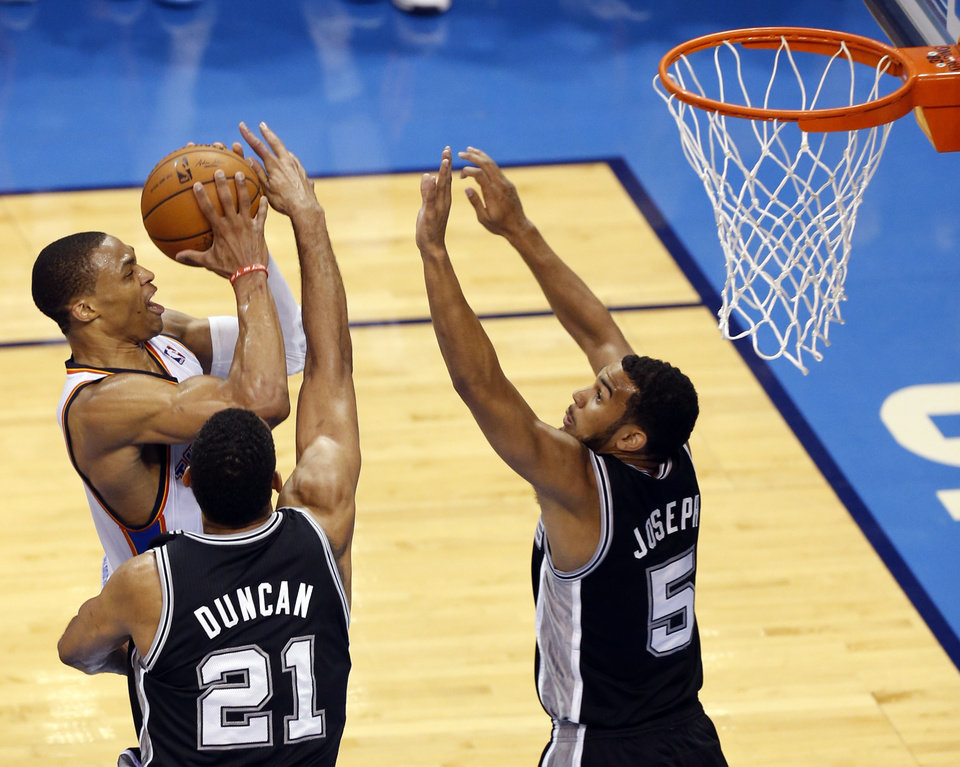 Photo - Oklahoma City's Russell Westbrook (0) goes to the basket as San Antonio's Tim Duncan (21) and San Antonio's Cory Joseph (5) defend during Game 6 of the Western Conference Finals in the NBA playoffs between the Oklahoma City Thunder and the San Antonio Spurs at Chesapeake Energy Arena in Oklahoma City, Saturday, May 31, 2014. Photo by Nate Billings, The Oklahoman