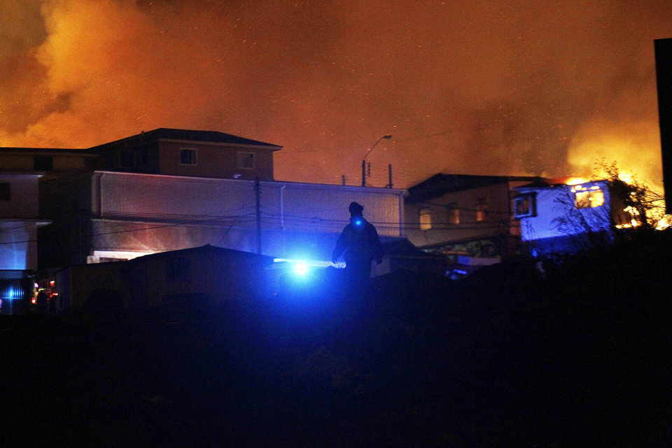 Photo - A policeman walks away as a forest fire rages towards urban areas in the city of Valparaiso, Chile, Sunday April 13, 2014. Authorities say the first fire has destroyed at least 150 homes and is forcing evacuations. (AP Photo/ Luis Hidalgo)