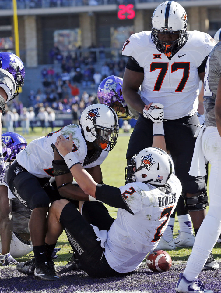 Photo - OSU's Justice Hill (27) and Victor Salako (77) help Mason Rudolph (2) up after a score during the second half of a college football game between the Oklahoma State University Cowboys (OSU) and the TCU Horned Frogs at Amon G. Carter Stadium in Fort Worth, Texas, on Saturday, Nov. 19, 2016. Photo by Steve Sisney, The Oklahoman