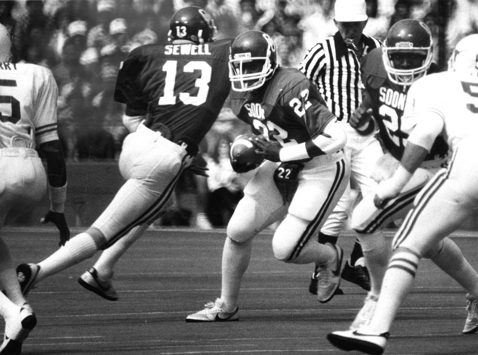"""Photo -  """"OU's Marcus Dupree (22)  fakes to Steve Sewell, then sets sail on a 63-yard touchdown run"""" against Texas in the Cotton Bowl.  The Sooners beat the Longhorns 28-22. Staff photo by Jim Argo taken 10/09/82; photo ran in the 10/10/82 Daily Oklahoman. File:  Football/OU/OU-Texas/Marcus Dupree/1982"""