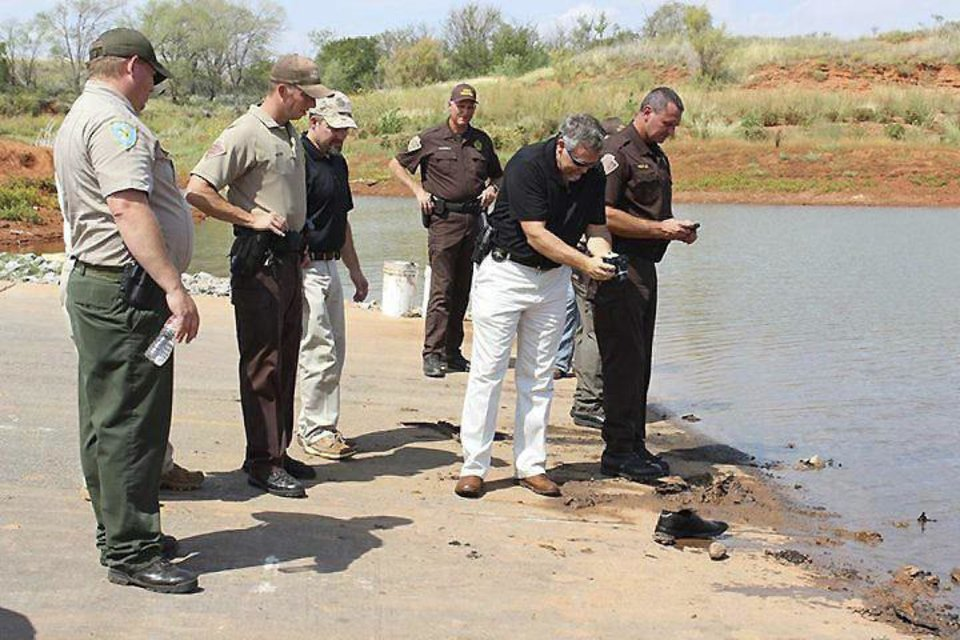 Oklahoma State Bureau of Investigation Special Agent Danny Sanders photographs a shoe discovered in Foss Lake, believed to be from one of two submerged vehicles pulled out of the lake Tuesday. AP Photo by Larissa Graham, The Elk City News <strong>Larissa Graham</strong>