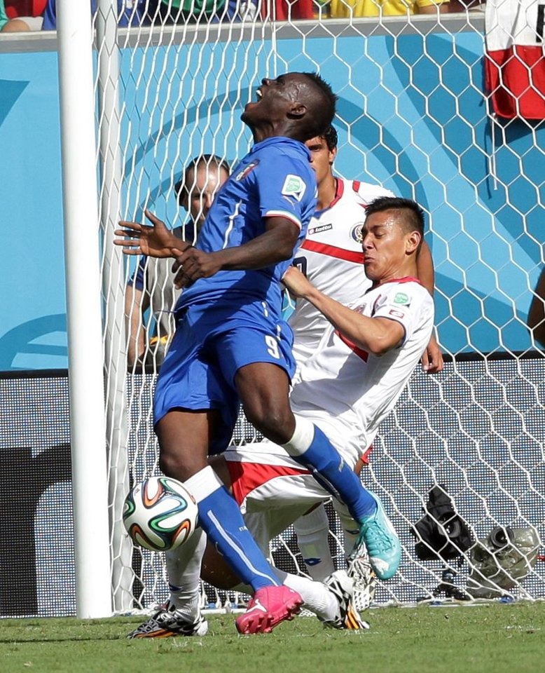 Photo - Italy's Mario Balotelli, left, claims a penalty after a challenge from Costa Rica's Oscar Duarte during the group D World Cup soccer match between Italy and Costa Rica at the Arena Pernambuco in Recife, Brazil, Friday, June 20, 2014. No penalty was awarded. (AP Photo/Antonio Calanni)