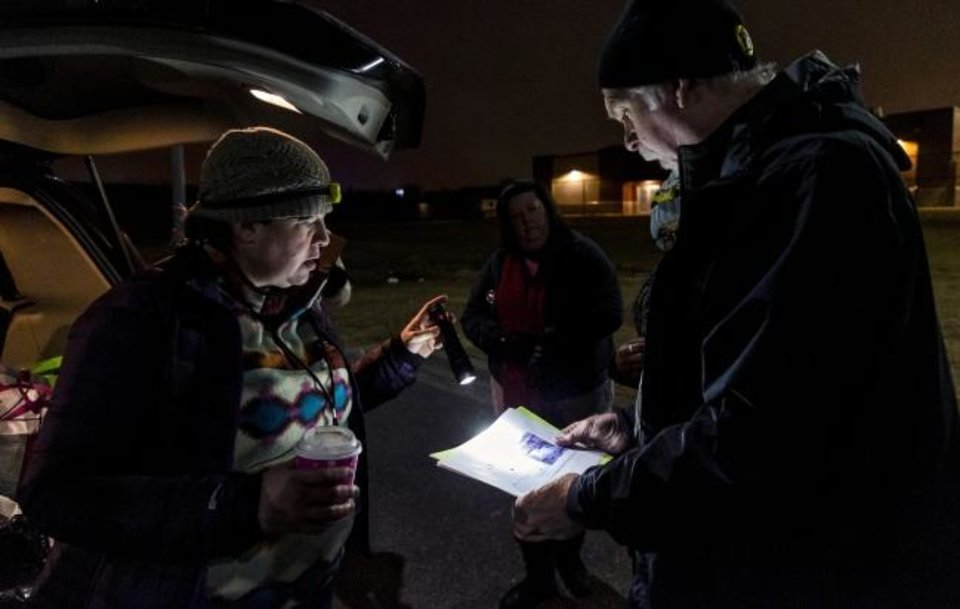 Photo -  Amy Newberry and Bob Mann look over a map as they visit homeless camps early Thursday. [Chris Landsberger/The Oklahoman]
