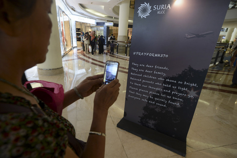 Photo - A Malaysian Chinese woman takes pictures of a message board for the missing Malaysia Airline, Flight MH370 with a mobile phone camera at a shopping mall in Kuala Lumpur, Malaysia, Monday, March 24, 2014.  A Chinese plane on Monday spotted two white, square-shaped objects in an area identified by satellite imagery as containing possible debris from the missing Malaysian airliner, while the United States separately prepared to send a specialized device that can locate black boxes. (AP Photo/Joshua Paul)